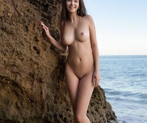 Solo woman Alisa I wanders a sandy shoreline while showing..