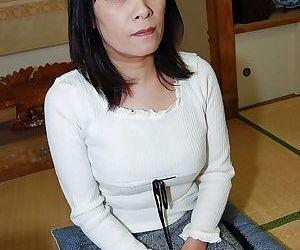 Asian milf Yumiko undressing her..