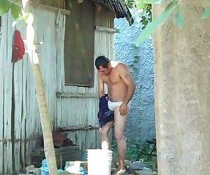 Graba al vecino hetero mientras se toma un baño en el patio