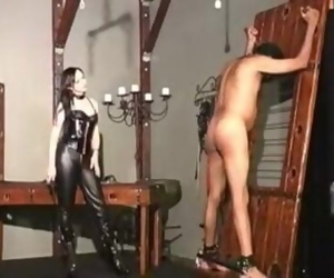 Mistress in black leather whipping male slave