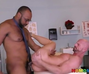 Black doctor removing something from the ass of a white guy