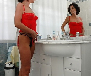 Seductive dark-haired granny unclothing off her..