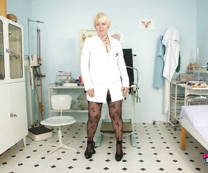 Nasty granny in nurse uniform opening up her images by her..
