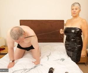 Mature woman in an assless latex dress paddles a mans..