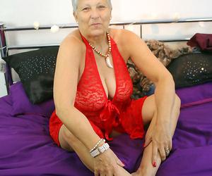 Mature granny Savana in crimson lingerie laughs as she..