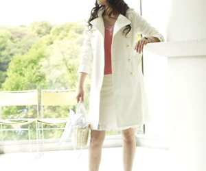 Clothed Japanese model Yuka Yamada shows her bare legs in a skirt