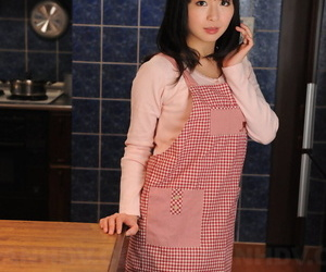 Japanese housewife with a pretty face poses non nude in her kitchen