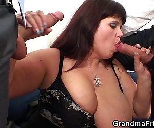 Busty mommy swallows two cocks..