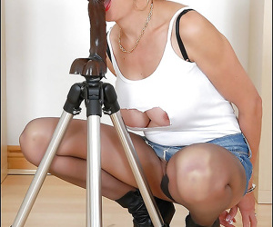 Handcuffed mature fetish lady in pantyhose playing with a dildo on a tripod