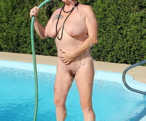 Naked old woman Mary Bitch wets her pierced bush with garden hose beside pool