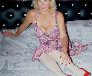 Older blonde woman hikes her dress over black panties in white stockings