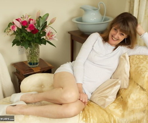 Older lady Pandora hikes her short dress over naked pussy in stiletto heels
