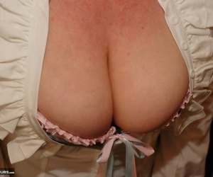 Mature woman exposes her big tits after slipping off leather skirt