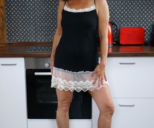 Brunette mature maid Mariana poses in uniform in the kitchen and shows cunt