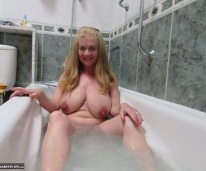 Mature woman Lilymay wets her big floppy tits & masturbates in the bathtub