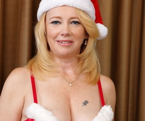 Mature woman Brandie Sweet keeps her Xmas cap on while modeling nude