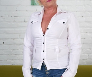 Glasses-clad mature granny Jessye sheds tight jeans to display nice tits & ass