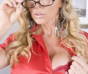 Hot mature model Dyanna Lauren takes off her glasses and begins to undress