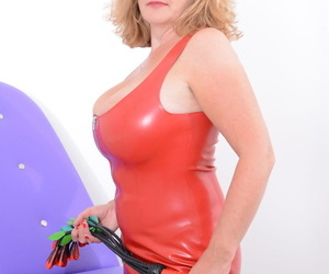 Busty mature blonde unzips a latex dress before toying her twat in latex boots