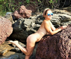 Older lady Diana Ananta models naked in sunglasses as the tide rushes in