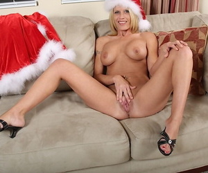 Nude mature vixen in Christmas hat pleasing her shaved twat with a vibrator