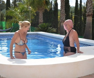 Mature blonde women frolic in a swimming pool with their swimsuits on