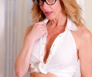 Mature woman Lana Wilder uncovers big tits before removing upskirt thong