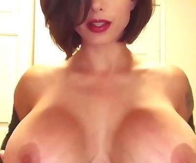 Amazing busty brunette rubs her huge fake tits