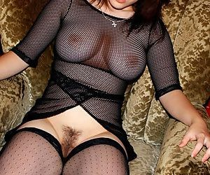 Bosomy asian babe with hairy cunt posing in sheer outfit..