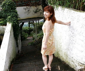 Redhead asian babe An Nanba stripping off her clothes..