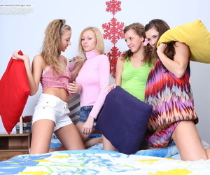 Young girls gather on a bed for a..