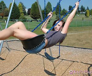 Teen amateur takes a swing on swing set in short denim..