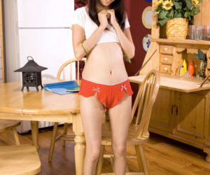 Young Asian girl toys her tight pussy on kitchen table in..