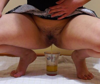 Girl with by a pussy hairy, pissing into a glass and drink their urine