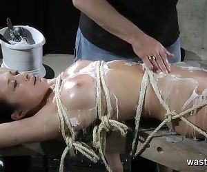 Bound nude gimp gets covered with scorching wax and given climaxes