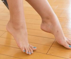 Youthfull bare Asian with bare feet providing a footjob to..