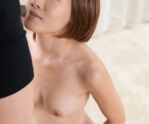Nude Asian female sucks a cock on her knees prior to a..