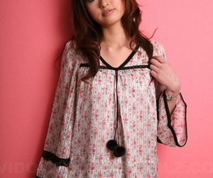 Japanese model with a pretty face stands clothed against a..