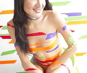 Colorful tape covers slender transsexual body during her..