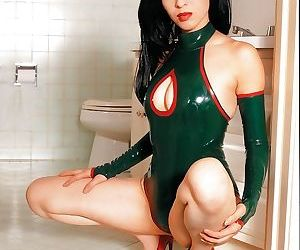 Playful asian babe slipping off her sexy latex outfit in..