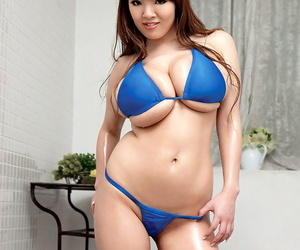 Asian model releases her massive tits from bikini top in..