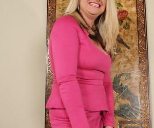 Older blond woman Mona Hawght peels off off pink office..