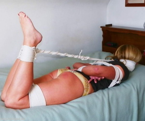 Light-haired girl is trussed up with rope and left gagged..