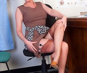 Mature teacher Holly Kiss strips to pose topless in..