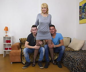 Blonde mature woman gets two boy toys to suck her big tits..