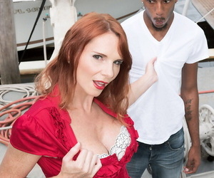 Older redhead April Skyz licks a BBC after being divested..