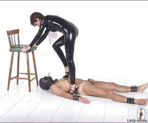 Lascivious femdom in latex outfit torturing her masked..