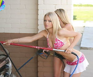 Blonde girl and her girlfriend wash a truck at the car..