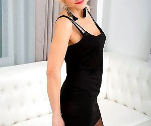 Milf blonde in black stockings poses on white sofa - part..