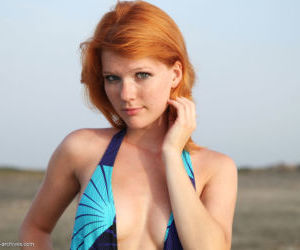 Freckled redhead Mia Sollis takes off her swimsuit as the..